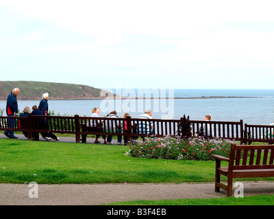 Visitors and holidaymakers,relax,looking over Filey bay towards 'Filey brigg'at Filey,North Yorkshire,England,uk. - Stock Photo
