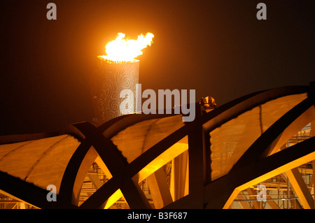 The Olympic torch burns above the Bird's Nest (National Stadium) during the Beijing 2008 Summer Olympic Games in - Stock Photo