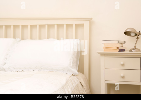 Empty bedroom with books on nightstand