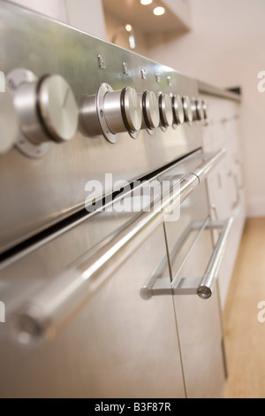 Empty kitchen with focus on stove dials - Stock Photo