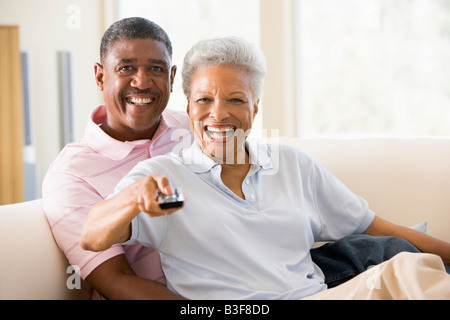 Couple in living room using remote control smiling - Stock Photo
