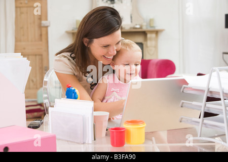 Mother and baby in home office with laptop - Stock Photo