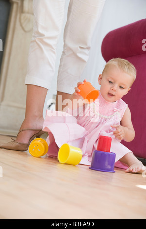 Mother in living room with baby playing - Stock Photo