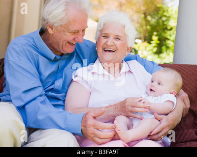 Grandparents outdoors on patio with baby smiling - Stock Photo