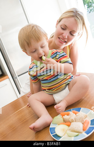 Mother and baby in kitchen eating fruit and vegetables - Stock Photo