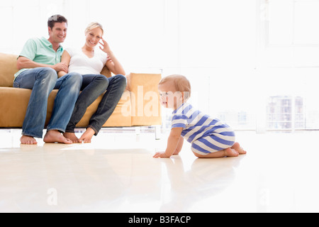 Couple in living room with baby smiling - Stock Photo