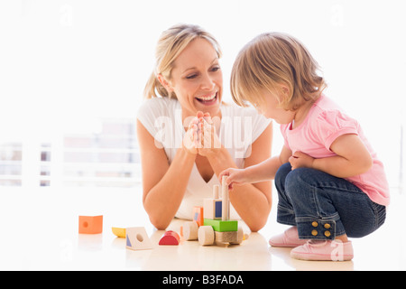 Mother and daughter indoors playing and smiling - Stock Photo