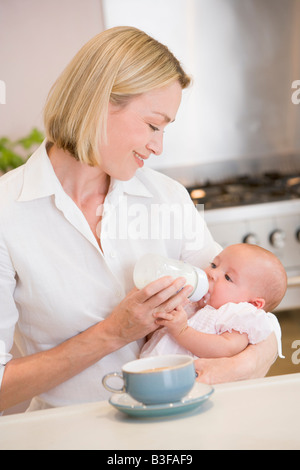 Mother feeding baby in kitchen with coffee smiling - Stock Photo