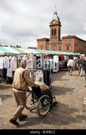 UK Derbyshire Chesterfield Town centre man pushing wheelchair bound wife through Market Square - Stock Photo