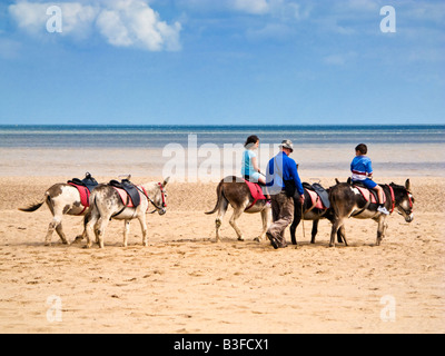 Small boy and girl riding donkeys on the sands at Skegness beach Lincolnshire England UK - Stock Photo
