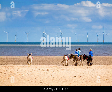 Children riding donkeys on the sands at Skegness beach, Lincolnshire, England UK - with offshore windfarm - Stock Photo