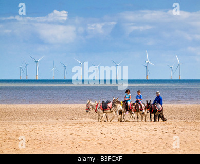 Small boy and girl riding donkeys on the sands at Skegness beach, Lincolnshire, England, UK with Offshore wind turbines - Stock Photo