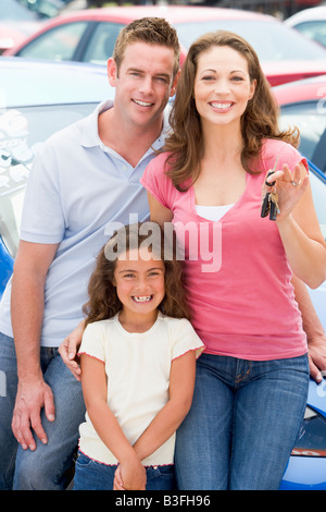 Mother Father and young daughter shopping for a new car - Stock Photo