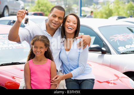 Mother and father with young daughter shopping for a new car - Stock Photo