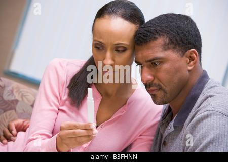 Couple with pregnancy test upset - Stock Photo