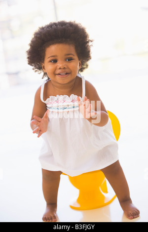 Baby indoors going on potty smiling - Stock Photo