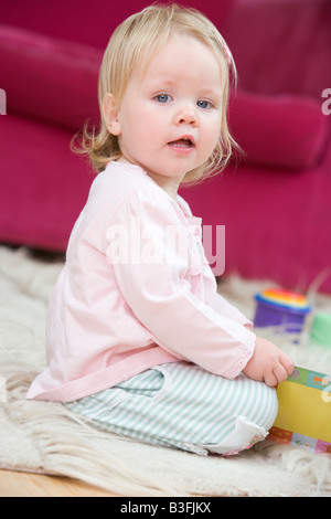 Baby in living room with toys and book - Stock Photo