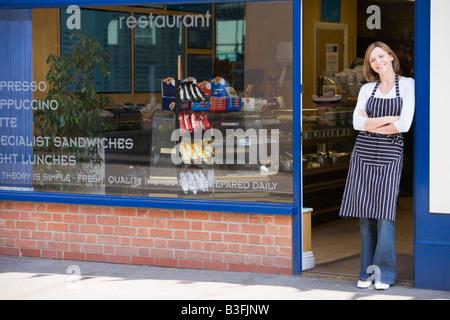 Woman standing in doorway of restaurant smiling - Stock Photo