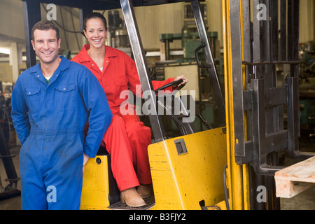 Two warehouse workers with forklift - Stock Photo
