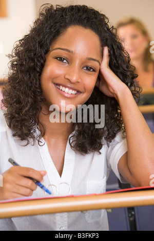 Student in class taking notes (selective focus) - Stock Photo