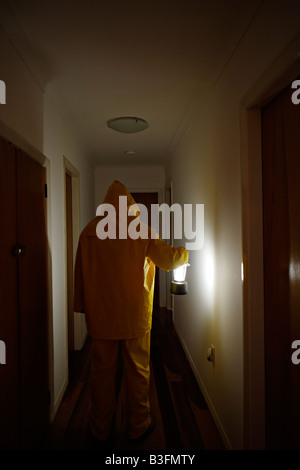 Man in corridor with lantern wearing wet weather gear - Stock Photo