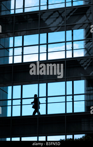 Royalty free photograph of business man walking in glass office building silhouetted against the evening sky. - Stock Photo