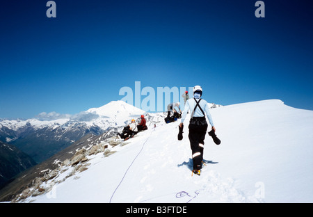 Mountaineers on summit of Mt Viautau (3820m). The twin summits of Mount Elbrus (5642m) in the background. Russia/North - Stock Photo