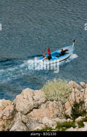 Traditional wooden fishing boat passing by (out of focus) nearby rocky Dalmatian terrain in Croatia - Stock Photo