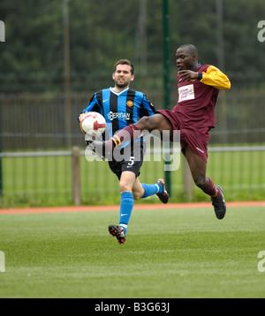 footballer  beats defender to lob the ball towards the goal - Stock Photo