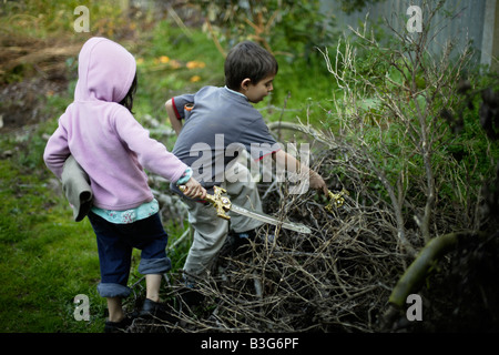 Boy aged six and sister five flush out imaginary foes from pile of tree cuttings with plastic toy swords - Stock Photo