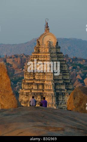Tourists enjoying the view from Hemakuta Hill onto Virupaksha Temple at sunset in Hampi Karnataka India 2005 - Stock Photo