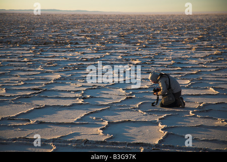 A tourists photographs the cracked earth surface at sunrise in the Salar de Uyuni salt flats in Bolivia. - Stock Photo