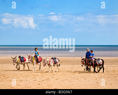 Small boy and girl riding donkeys on the sands at Skegness beach, Lincolnshire, England, UK - Stock Photo