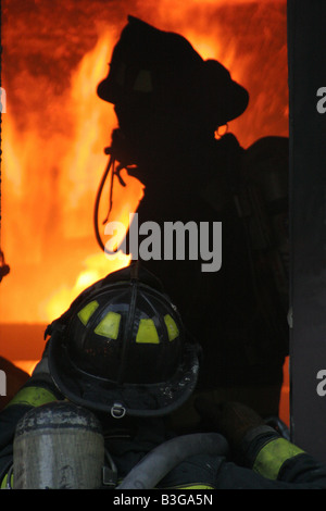 Three firefighters looking in on a room of a house on fire before putting out the flames - Stock Photo