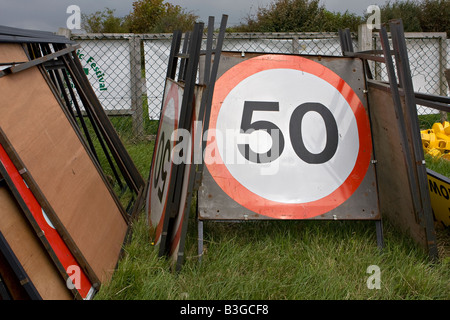 Pile of 50 miles per hour road signs stacked on the ground Sussex England - Stock Photo