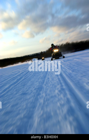 Movig snow-bikes on a frozen river in lapland - finland - Stock Photo