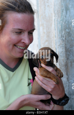 Younger smiling woman holding a puppy Villa Clara Province Cuba April 2007 - Stock Photo