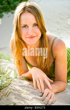 Portrait of pretty redheaded woman lying in sand looking at viewer - Stock Photo