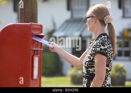 Woman posting letter - Stock Photo
