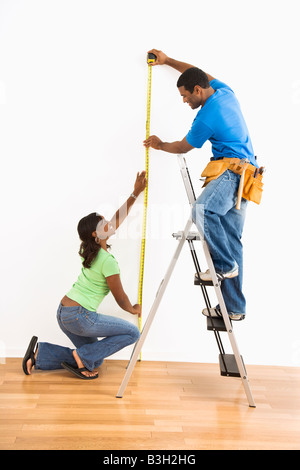 African American man and woman measuring wall at home - Stock Photo