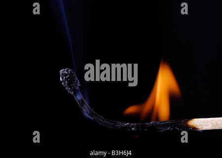 A lit wooden match burning down slowly - Stock Photo