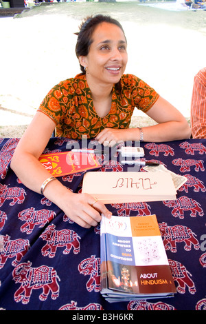 Indian American woman listening Hindu American Foundation Info table. Dragon Festival Lake Phalen Park St Paul Minnesota - Stock Photo