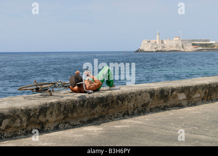 Cuban man with bicycle lying on a wall at the Malecon Boulevard in Havana Cuba April 2007 - Stock Photo