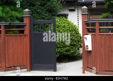 The front gate of a traditional house in Shimosuwa Nagano Japan with pruned shrubs and a rain chain September 2 - Stock Photo