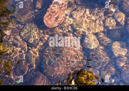 Ripples reflected onto shiny surfaces of rocks and pebbles in the River Enz in Germany's Black Forest - Stock Photo