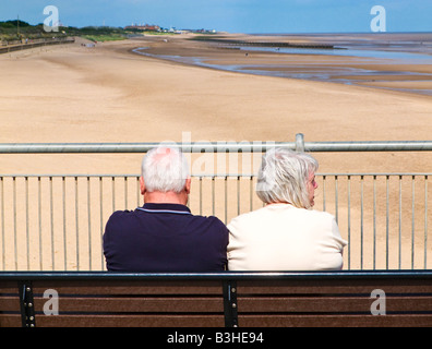 Senior couple tourists enjoying the view on the beach from Skegness Pier, from behind, Lincolnshire, England UK - Stock Photo