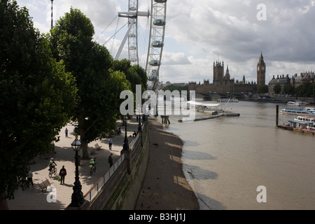 A low-tide River Thames people on Millennium Walk London Eye and the Houses of Parliament are seen from a high viewpoint - Stock Photo