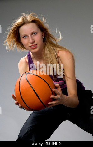 Young woman with basketball ball - Stock Photo