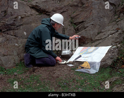 A geologist uses a geiger counter to check for radiation while examining rocks - Stock Photo