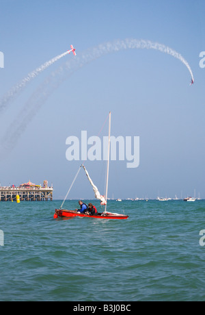 A couple in a sailing boat off Bournemouth beach, during the Bournemouth Air Festival. Bi-plane display over the - Stock Photo